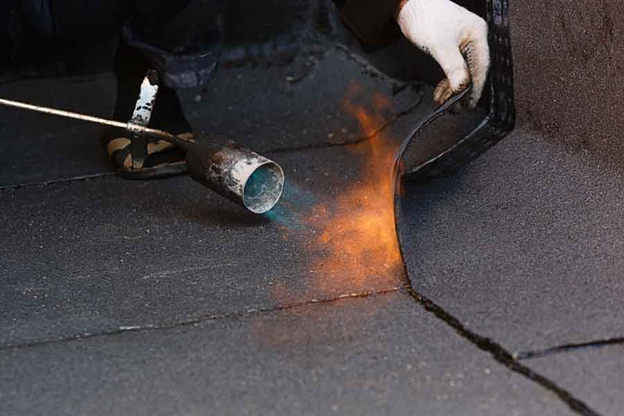 sheet torch on waterproofing being applied to prevent roof leakage